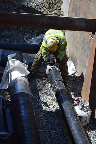 Welder installs shield on underground pipe
